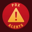 PDX Alerts logo with a red circle that has a yellow triangle and a red exclamation mark in the middle.